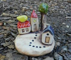 This cute village with a little yellow bird sitting on the roof is hand made out of white clay.   The sculpture measures approx. H 2 3/4 x W 2 3/4