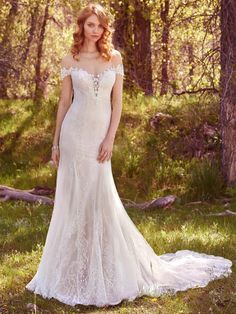 Maggie Sottero - SHAE, Beaded lace appliqués trim the illusion plunging sweetheart neckline, illusion off-the-shoulder sleeves, and illusion open-back in this romantic fit-and-flare. Featuring allover lace, a scalloped hemline, back ruching, and soft godets. Finished with covered buttons over zipper closure.