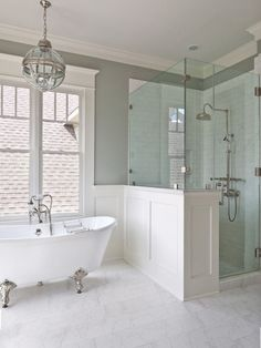 A gorgeous claw foot tub and glass-enclosed shower