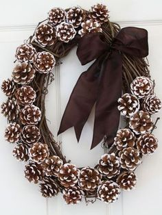 A grapevine weath covered with white tipped pine cones and a velvet bow @  http://goodideasforyou.com/mix-a-match/2181-diy-pine-cones-decoration.html