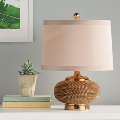 Perfect for flanking your sofa or bed, this eye-catching table lamp showcases a gold-hued finish and beaded base.