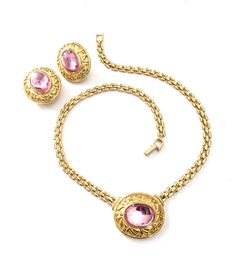 Trifari TM Pink Demi Parure  Measure: Approx. Necklace Chain 16L x 1/4W  Pendant 1 1/4W x 1T  Earrings 1 1/4T x 1W  Mark: Trifari TM  Condition: Very Good vintage condition  A beautiful Trifari demi parure of a stunning necklace and matching clip-on earring set. The pendant and the earrings have a stamped foliate gold surrounds that frame the exquisite pink glass cabochons. Trifari reissued some of their favorite designs and they were marked with TM following the Trifari signat...