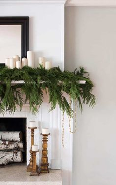 I love how free and natural this mantle greenery looks. The simple white candles… I love how free and natural this mantle greenery looks. The simple white candles layered into the greenery create a simple and laidback Christmas look. Christmas Mantels, Noel Christmas, Christmas Crafts, Christmas Fireplace Garland, Vintage Christmas, Christmas Greenery, Christmas Wreaths, White Christmas Garland, Vintage Santas