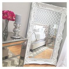 Gorgeoys mirrired furniture with big white ornate mirror. Pink flowers pop against the neutrals