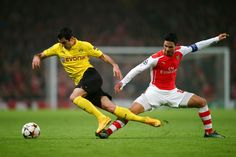 Henrikh Mkhitaryan of Borussia Dortmund is brought down by Mikel Arteta of Arsenal during the UEFA Champions League Group D match between Arsenal and Borussia Dortmund at the Emirates Stadium on November 26, 2014 in London, United Kingdom.
