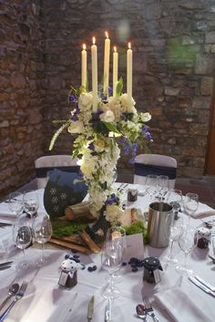 "The ""Verdi Gris"" Candelabra dressed with a garland of fresh Hydrangeas, Roses, Tulips, Delphiniums, Antirhinnums, Wax Flower Blossom and Thalaspi"
