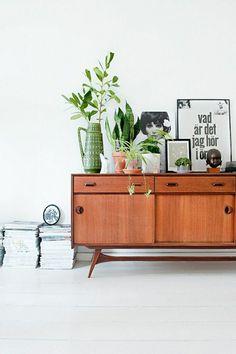 hölzerne Kommode und viele Pflanzen in diesem Wohnzimmer mit skandinavischem Design