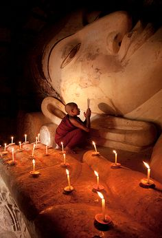 A Buddhist monk prays by candlelight in a temple in the ancient city of Bagan, Myanmar (Burma) ~ photograph by »Kyle Hammons
