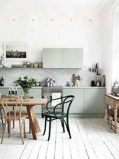 Cocina con comedor de diaro. Mesa de madera en color natural, sillas de madera color natural y pintadas en verde oscuro. Muebles de cocina en verde claro muy pálido. Muros y cielo blanco.