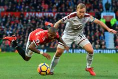 Manchester United's English midfielder Ashley Young goes down in a challenge with Burnley's Scottishborn Canadian midfielder Scott Arfield during the...