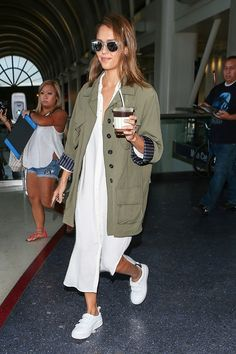 Jessica Alba wears a white dress, army jacket, white velcro sneakers, and clear-frame sunglasses