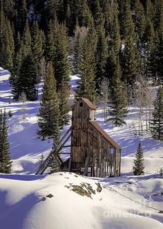 The old Idarado Mine sits abandoned on the Mountain Slope in colorado Winter.  The Idarado Mine was a gold mining operation in the San Juan Mountains of Ouray County, Colorado. The mine is within the Sneffels-Red Mountain-Telluride mining district. The remains of the operation are visible from the Million Dollar Highway, north of Red Mountain Pass, between Ouray and Silverton, Colorado.