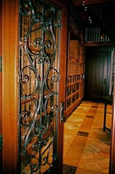 Narrow spaces can work well for a wine room. Perfect wrought iron door here!