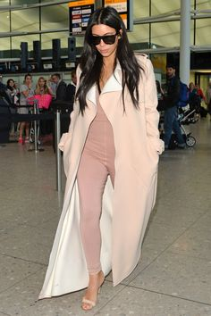 Pregnant Kim Kardashian wears a skintight pink unitard to Heathrow airport with a Burberry trench coat thrown over the top...