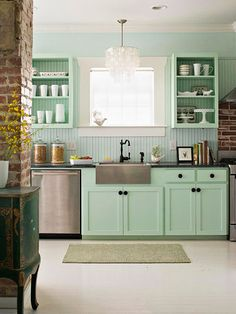 Mint cabinets, open shelving, stainless farmhouse sink. Capiz chandelier, exposed brick. LOVE everything.