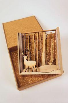 Caja elaborada en madera diseñada en capas que generan profundidad con el escenario de un bosque.