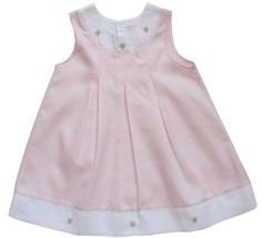 Fine white and pink embroidered girls dress with tucks and pink embroidery in the front. Made in 100% peruvian cotton. Very luxurious.