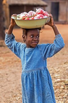 girl returning from market with vegetables on her head, Chief Mukuni Village, Zambia