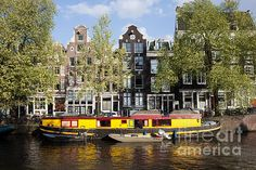 Historic row houses and barge converted houseboat on a canal in Amsterdam, Holland, Netherlands.