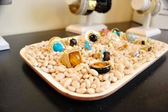 Your showcase: Nestle rings in a tray of beans... copper necklaces in river rocks... bright bracelets in clear glass pebbles. Makes #consignment jwlry look like treasures!