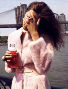 Womens editorial fashion photo shoot: pink fur coat jacket, pink leather belt, vitamin water drink (gg)