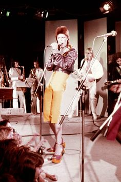 A trippy version of a Katharine Hepburn ensemble, Bowie wears his high-waisted trousers and blouse with finesse. Bowie Ziggy Stardust, David Bowie Ziggy, Glam Rock, David Bowie Fashion, David Bowie Pictures, Ziggy Played Guitar, Moonage Daydream, Terry O Neill, Mick Ronson