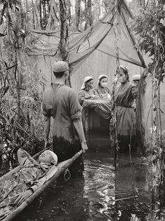 A Cambodian guerrilla is carried to an improvised operating room in a mangrove swamp on the Ca Mau Peninsula