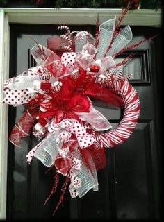 The lighting doesnt do this wreath justice - the colors POP in this wreath and it has just the right about of sparkle to make your season merry AND bright!  A foam wreath is wrapped in glittery peppermint stripe satin ribbon and accented by a huge spray of red, white, and peppermint stripe deco mesh curls, and swirls of ribbon in polka dot, peppermint candy and red & silver filigree designs, peppermint-themed sequin ting ting spirals, glittered sprays of candy canes, peppermint disks and…