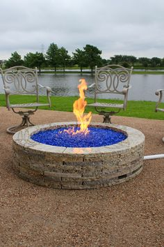 """48"""" granite fire pit with 20lb propane tank conversion kit and sky blue Eco fire glass."""
