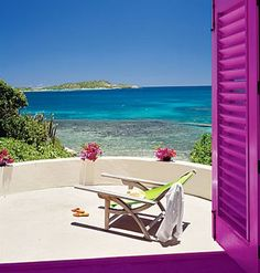 Nice balcony overlooking the ocean!   Love the flowers and purple shutters!