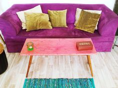 Love this colours- purple couch, vintage cushions and pink wooden bench as a coffee table.