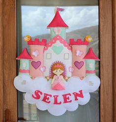 Bu özgün prenses kapı süsü modelini en sevdiğim pastel tonlarda renklerden oluşturduk. Gerçekten hazırlık sürecinde renk seçimi, ebat büyüklüğü, süslemelerin neler olacağı konusunda hayli bir zaman ve emek harcadık.  Emeğimizin sonunda nihayet prenses kapı süsü modelini çıkardık. Biz bu modeli kız bebek odaları için çok güzel olacağını düşünüyoruz. Umarın sizler de beğenirsiniz:)  Prensesimiz bulutlar üstünde bir şatoda yaşıyor:) Üstelik bulutun üstünde prensesimizin ismi yazılı:)  Keçeden…