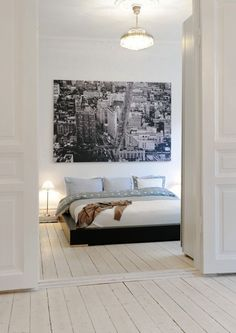 Unframed art like this black and white cityscape is gorgeous in a contemporary or eclectic bedroom. Temporary wall murals are readily available online right now. Its easy to find one you love. From verdant green forest to ancient ruins, its a great look. Without bedside tables, tall metal buffet lamps with tiny shades provide light and are a pretty look.