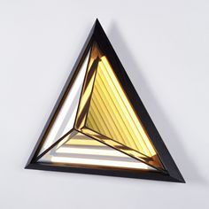 """STELLA TRIANGLE  DESIGNER: ROSIE LI   MANUFACTURER: ROLL & HILL  MATERIALS: BRASS, MIRRORED GLASS, STEEL, WOOD  DIMENSIONS: W 17 x D 6.5"""" x H 19.5""""   DESCRIPTION: Inspired by his early work, this sconce is named after the painter Frank Stella. When illuminated, its half-mirrored glass diffuser reveals a series of nested geometric shapes. Stella creates the impression of infinite volume within a finite space. Bulb: 120V Illumination LED"""