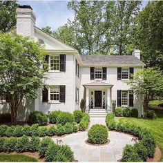 Great landscaping and walkway to the front door. Greenery with White House and black shutters