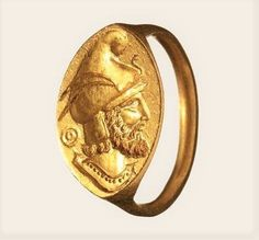 A Greek gold seal ring, 4th century B.C. Slender shank ridged on the side, with pointed oval plate. Thereupon the deeply engraved bust of a Phrygian warrior with full beard. The typical helmet with two feathers on the side and decorated with a snake on the front side. Impressive engraving. Diameter 2.4 cm, weight 12 g.