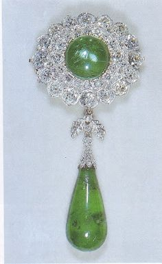 Queen Mary's Emerald Brooch I Part of the Cambridge Emeralds, this cabochon emerald is surrounded by 2 rows of diamonds with an emerald drop