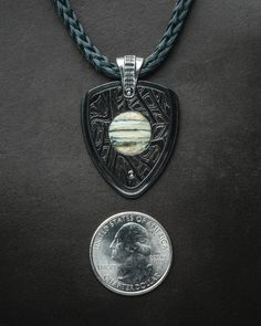 The Apollo pendant, inspired by the timeless form of a guitar pick, has a beautiful story to tell.  The center is inlaid with wooly mammoth tooth that is at least 10,000 years old, harvested from the seafloor. Surrounding the fossil mammoth tooth is hand-forged damascus steel, made by forging and patterning 125 layers of different alloy steel into a remarkable and unique metal tapestry.  All housed in a stainless body coated with black diamond, and presented on a braided Kevlar cord with…