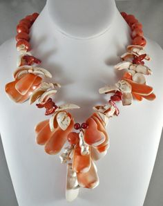 Lots of peachy colored shells adorn this necklace with a sprinkling of freshwater pearls intermixed. Peach coral beads adds additional interest. Necklace