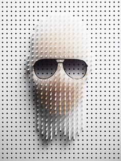 """Karl Lagerfeld. Sculpted portraits of famous people created by photographer Philip Karlberg for Plaza Magazine. Mr Karlberg used approximately 1200 carefully arranged wooden pins and clever lighting to recreate faces of """"classic wearers of sunglasses"""". Scuplting and shooting took 6 days for the 6 faces."""