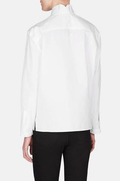 """""""I wanted clothing that defied trends and I would wear for twenty years and never want to give away,"""" says Susie Crippen of her motivation to go solo after leaving J Brand. That ethos is demonstrated by this elegant take on the classic white cotton button-up. The topstitched shawl collar has a foldover back detail that echoes the overlapping v-neck, which transitions to a three-button placket. Finishing touches include a back yoke, button cuffs, and a side-slit hem."""