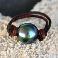 ...a single black Tahitian pearl brings a wonderful spot of irridescent color to this pearl and leather ring and looks beautiful against any skin tone...