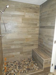 Wood plank Porcelain tile Shower with full width bench, 2 fabricated corner caddies, and flat rock pan. Installed by BP'S TILE.