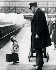 Very young passenger asks a station attendant for directions, on the railway platform at Bristol, England, 1936. Photo by George W. Hales.