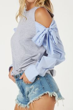 Cold shoulder sweater with relaxed fit. Contrast sleeves with stripe patterns and ties for added detail.