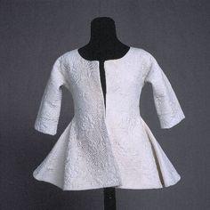 Quilted linen shortgown, ca 1750.  KM 2463 :: kofta  Vit, matelasserad i blommor, blad och långa slingrande stjälkar. Halvlång ärm, vilken går i ett stycke med rygg och framstycke, s.k. kimono-modell. Brunfläckig (nov. 1994).