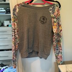 """Gray billabong pullover sweatshirt Body color gray. Sleeves multi floral. Ribbed crew neck.says """"sharks beach lover for life"""" on gray part. It's pilling a little on gray part. Billabong Tops Sweatshirts & Hoodies"""