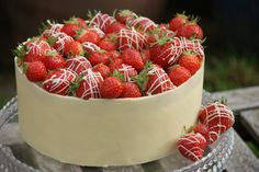 White Chocolate Mud Cake with white chocolate frosting wrapped with a chocolate collar and topped with fresh juicy British strawberries.