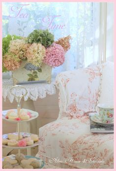 Tea Time. Round linen and lace topper on table. Magazine rack painted with tole and filled with hydrangeas. Toile fabric.