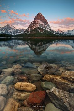 Grinnell - This is Swiftcurrent Lake and Mount Grinnell in Glacier National Park, Montana, in early Spring before the park officially opened. Shot with a wide angle lens several inches from my foreground. 3 focus points blended in Photoshop to achieve the sharp depth of field from foreground to background that I was after.